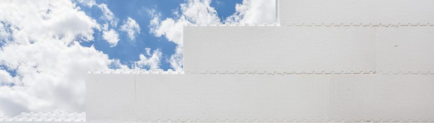 Photo of incomplete styrofoam polymer wall against beautiful calm peaceful blue sky outside new comfort building