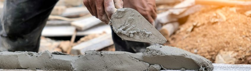Close up of a worker putting cement into the brick wall at construction site